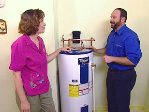 jack has just finished installing the new water heater and talks with the client
